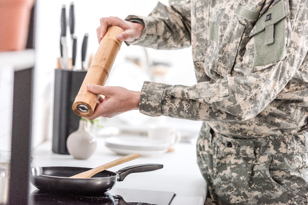 cropped view of army soldier using pepper pot while cooking in kitchen