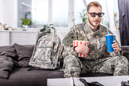 handsome soldier in 3d glasses on couch watching movie with popcorn and soda water