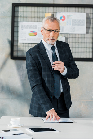 handsome middle aged businessman in suit standing near table and looking at camera in office