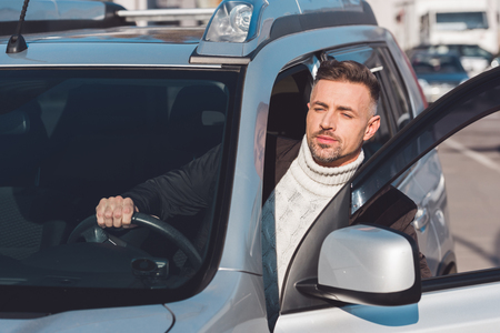 Handsome man looking out from car and holding steer