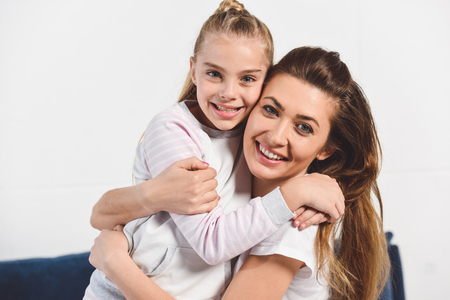 Mom and daughter embracing and smiling at home