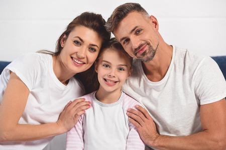 Happy smiling parents hugging daughter in pajamas
