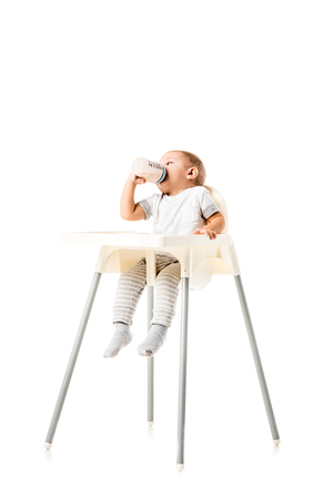 Cute toddler boy drinking from baby bottle and sitting in highchair isolated on white