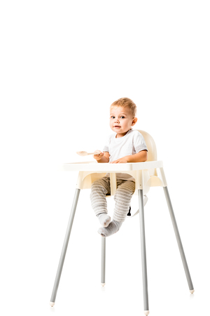 Cute toddler boy sitting in highchair and looking at camera isolated on white