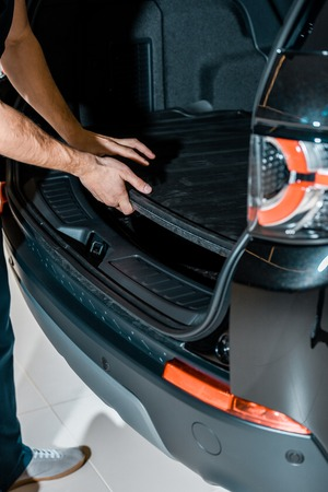 Partial view of auto mechanic checking car trunk at auto repair shop