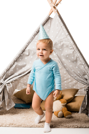 Toddler boy in party hat standing in front of wigwam with pillows and teddy bear isolated on white Stock Photo
