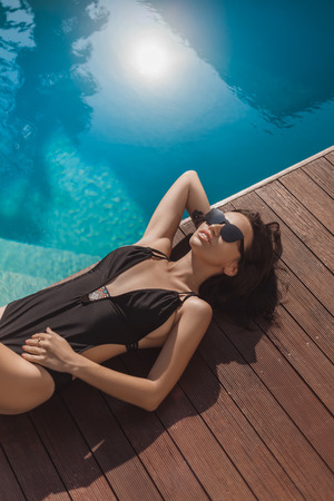 High angle view of young woman in black swimsuit lying at poolside Stock Photo