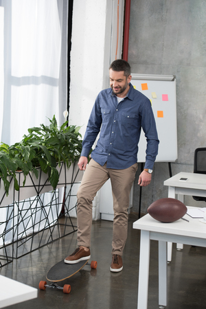 Cheerful handsome businessman putting leg on longboard in office Imagens