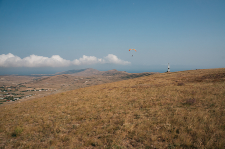 Parachute in the sky over field in hillside area of Crimea, Ukraine.