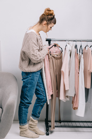 Side view of girl standing near stand and choosing what to wear Standard-Bild