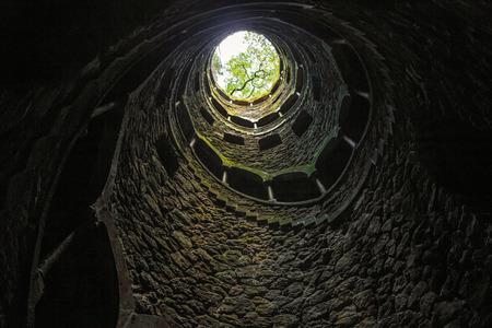 Vista inferior de la luz y los árboles al final de las escaleras de caracol, Portugal, Quinta da Regaleira Foto de archivo