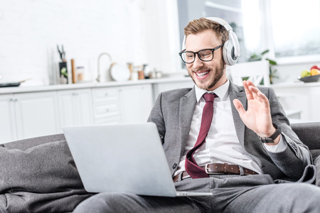 Businessman in glasses wearing headphones, waving with hand and using laptop on couch
