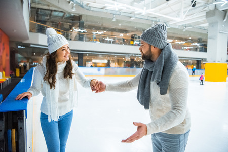 Smiling couple in hats and sweaters holding hands while skating on ice rink Stockfoto - 112758521