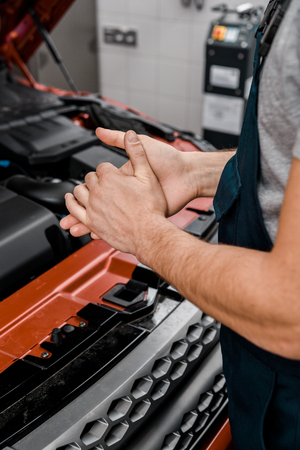 Cropped shot of repairman standing at car with opened cowl at auto repair shop Stock Photo