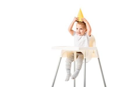Cute toddler boy sitting in highchair and putting yellow party hat on head isolated on white Stock Photo