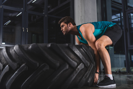 Sportsman lifting tire during cross training in sports center