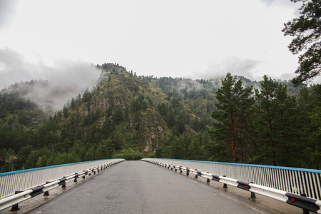 Beautiful mountain landscape and asphalt road at cloudy day, Altai, Russia
