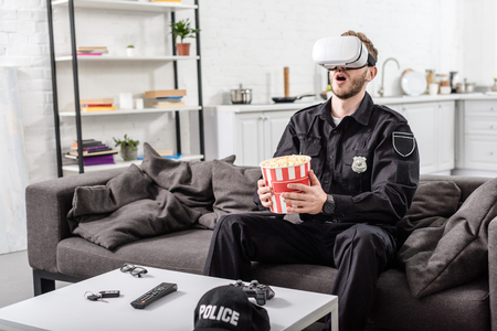Surprised police officer with virtual reality headset on head holding striped popcorn bucket and sitting on couch