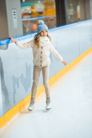 Little child in knitted hat and sweater skating on ice rink