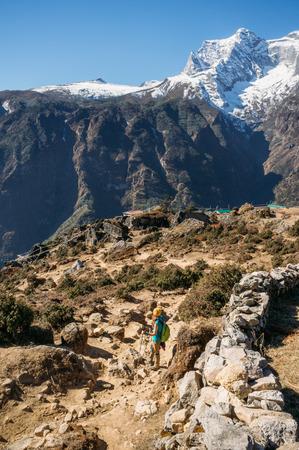 Woman walking among Nepal mountains peaks, Sagarmatha. Stock Photo