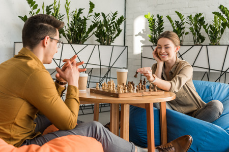 Young happy couple playing chess while sitting on beanbags Stok Fotoğraf - 112758325