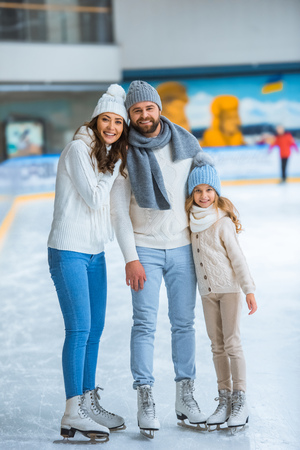 Smiling parents and daughter in sweaters looking at camera on skating rink