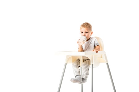Adorable toddler boy sitting in highchair and drinking from baby bottle isolated on white Stock Photo
