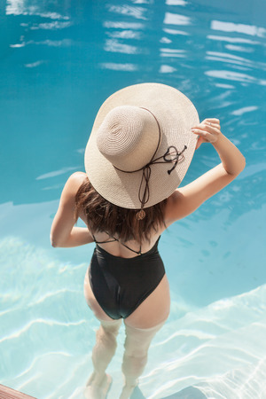 Back view of young woman in swimsuit and hat standing in pool