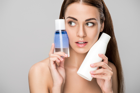 Beautiful girl with perfect skin holding two bottles with makeup remover, isolated on grey