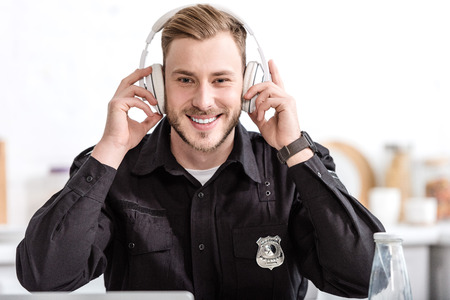 Police officer smiling and listening to music with headphones at kitchen