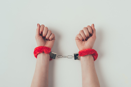 Cropped image of woman hands in red fluffy handcuffs on white