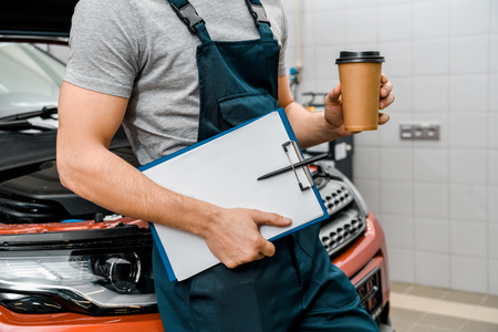 Partial view of male auto mechanic with notepad and coffee to go near car at auto repair shop Stock Photo - 112758558