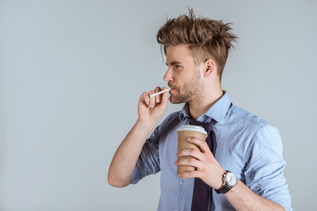 Tired businessman holding paper cup and smoking cigarette isolated on grey