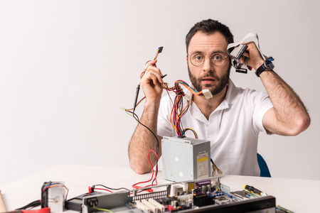 Bewildered man holding wires and computer parts in hands Stock Photo