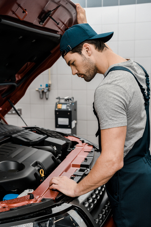 Side view of repairman examining car with opened cowl at auto repair shop Stock Photo - 112758910