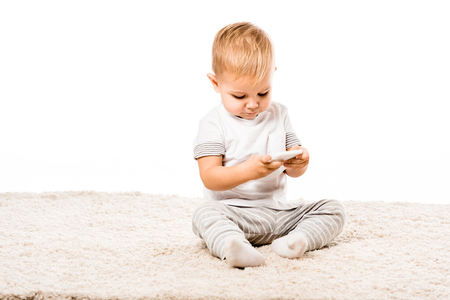 Adorable little boy with smartphone sitting on carpet isolated on white