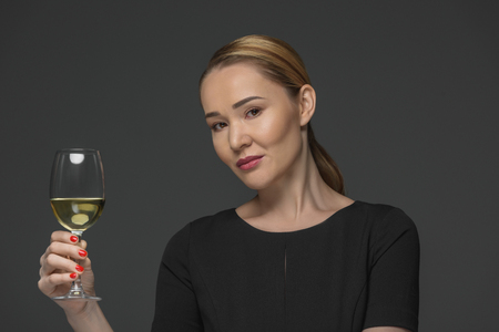 Smiling Kazakh woman holding glass of wine and looking at camera isolated on grey Stok Fotoğraf