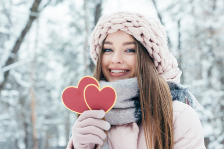 Portrait of beautiful young woman with hearts in hand looking at camera in snowy park Stock Photo