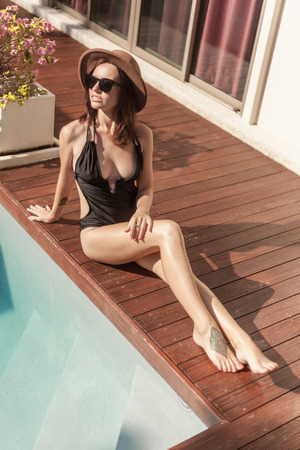 Attractive young woman in swimsuit and hat sitting at poolside