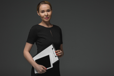 Beautiful Kazakh businesswoman with digital tablet and clipboard smiling at camera isolated on grey
