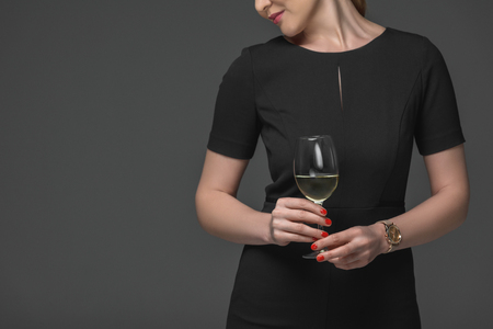 Cropped shot of elegant woman in black dress holding glass of wine isolated on grey