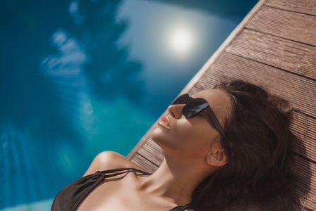 Close-up portrait of relaxed young woman in black bikini lying at poolside
