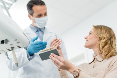 Doctor showing tooth implants to female patient in modern dental clinic Stock Photo