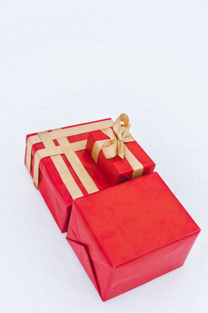 Close-up view of red gift boxes with golden ribbons isolated on grey