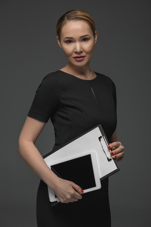 Beautiful Kazakh businesswoman with digital tablet and clipboard looking at camera isolated on grey Stok Fotoğraf - 112758787