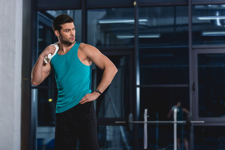 Sportsman standing with towel after training in gym Stock Photo