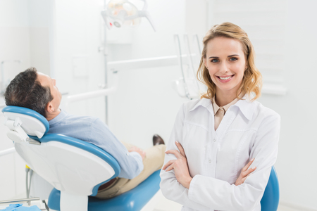 Female doctor with folded arms in modern dental clinic