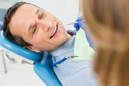 Dentist checking patient teeth in modern clinic