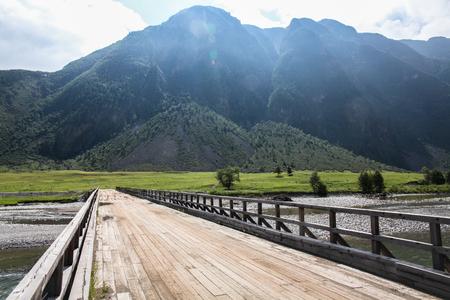 Mountain landscape with river and wooden bridge, Altai, Russia Stock Photo