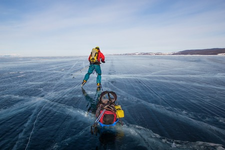 Male hiker with backpack walking on ice water surface, Russia, lake Baikal